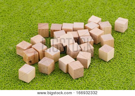 Wooden cubes on the green plastic background.