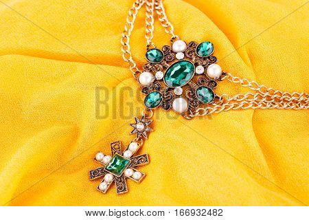 Stylish necklace with green stones and pearls on fabric background.