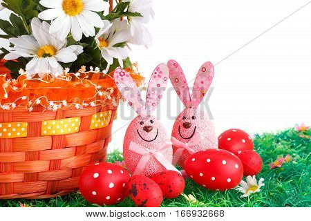 Easter decoration with bunnies eggs and flowers in basket on artificial grass.