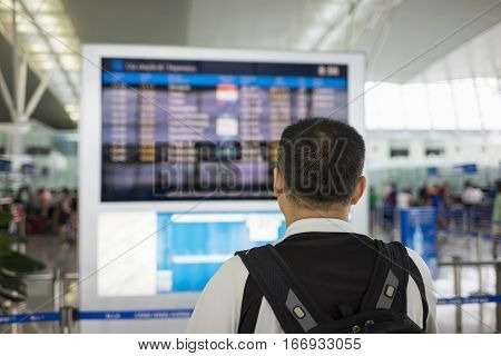 Back View Of A Man Looking At Flight Timetable At Airport
