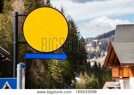 Round empty sign with arrow. Yellow circle and blue arrow pointing. Mountain landscape.