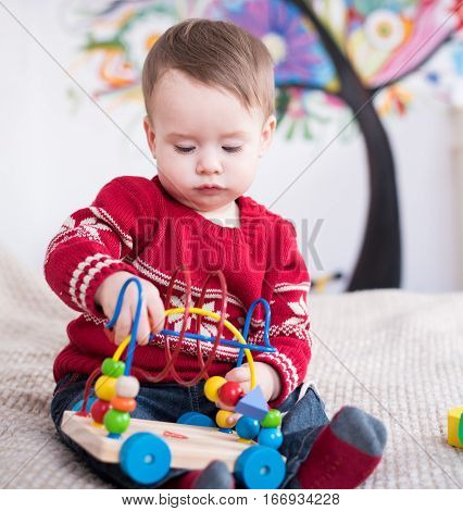 Kid boy playing with educational toy at home. Cute little kid boy playing developing games for kids. Happy child playing colorful toys. Educational toy. Developing games.