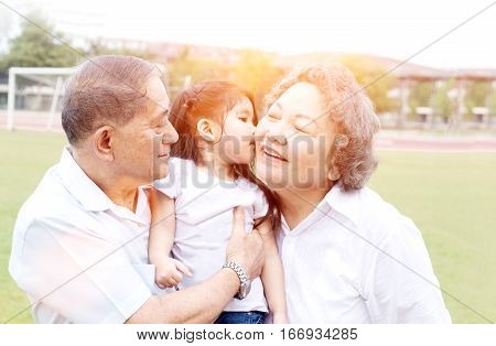 asian grandfather and grandmother hug children in sport park