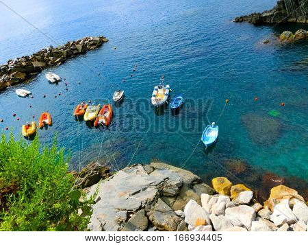 Colorful fish boats on a rock over Mediterranean sea at Manarola, Cinque Terre, Italy