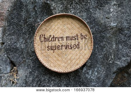 Children Must Be Supervised wrote on bamboo basket and hanging on rock
