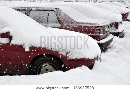 Many parked cars covered with snow after snowfall in winter. Side view.