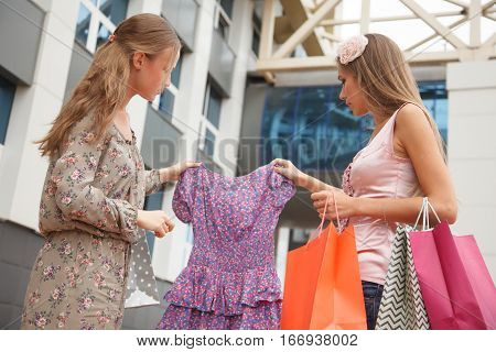 Two girls with shopping bags standing on the streetone of the girls envies of new dress another girl