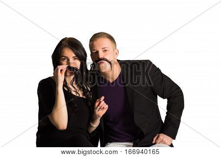 Feeling playful. Beautiful young loving couple bonding to each other and smiling while making a fake mustaches from her hair