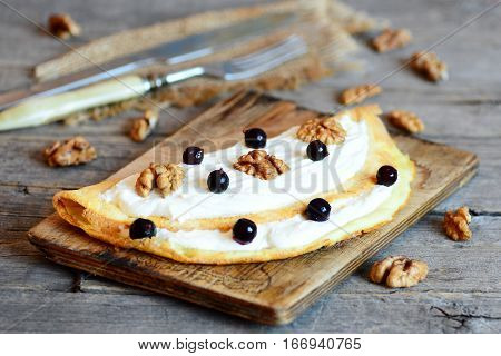 Homemade fried omelette with cottage cheese, walnuts and berries on a wooden board. Sweet berry breakfast omelette. Kids breakfast menu. Rustic style. Closeup