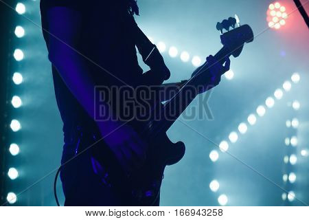 Bass Guitar Player In Blue Stage Lights
