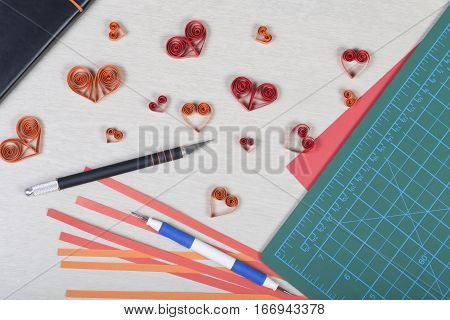 Handmade paper hearts with tools for quilling (paper strips slotted tool knife cutting mat) on light wooden background. Preparation for Valentine's day wedding or other romantic event. Top view.
