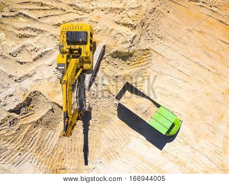 Aerial view of a excavator loading a truck in the mine or on construction site. Heavy industry from above.