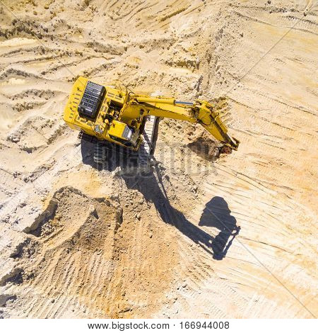 Aerial view of a working excavator in the mine. Industrial background on mining theme.