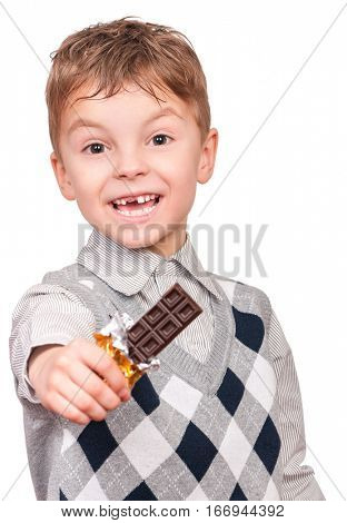 Funny little boy eating chocolate. He is smudged with chocolate. Child isolated on white background.