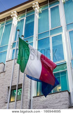 Italian flag hoisted with modern building on the background