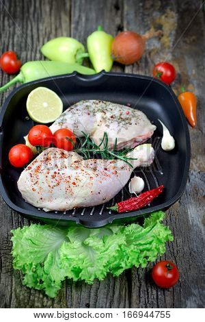 Raw chicken meat - raw chicken drumstick and raw chicken breast with spices in pan on rustic table