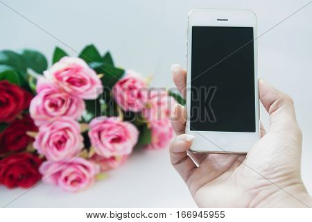 Woman hand holding mobile phone with rose bouquet background