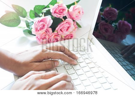 Woman using laptop computer with pink rose bouquet. Shopping on line Valentine's day