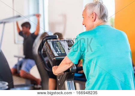 Senior woman spinning on sport bike in fitness gym club circle training session