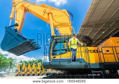 Asian driver standing on construction machinery on building site