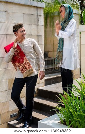 Asian Muslim man going to work leaving housewife woman wearing traditional dress