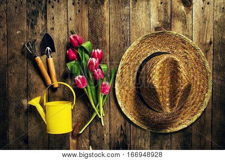 Gardening tools flowers watering can rubber boots and straw hat on vintage wooden table. Spring summer or garden concept background top view.
