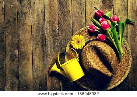 Gardening tools flowers watering can and straw hat on vintage wooden table. Spring summer or garden concept background with free text space.