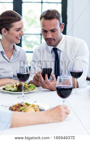 Business colleagues looking at mobile phone during business lunch meeting at restaurant