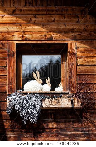 Window on wooden house, decorations and rabbit shapes. Pretty window of a wooden mountain house. Some silhouettes of rabbits, flowers and plants in wooden vase.