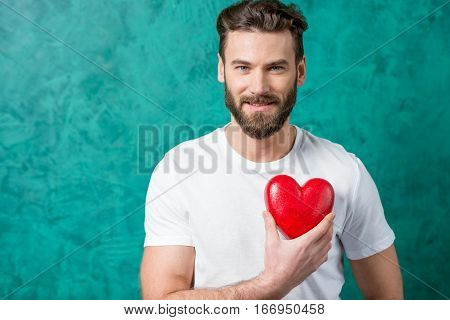 Handsome man in the white t-shirt holding red heart on the painted green wall background. Valentine's Day concept