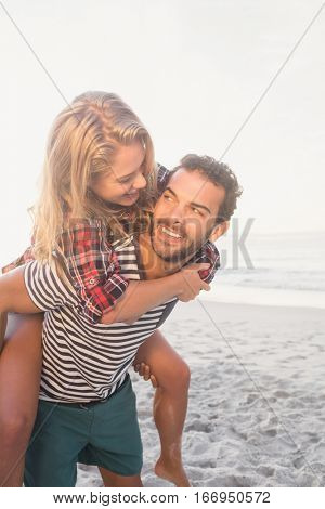 Portrait of a young man piggybacking beautiful woman on the beach