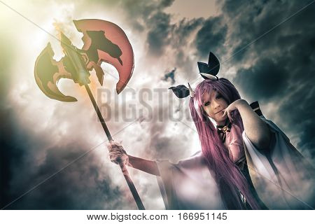 Devil young woman with spear pitchfork, hell demon in cloudy sky. A young girl dressed as demon or devil. The woman holds a pitchfork in her hand. Behind her a sky covered by clouds.