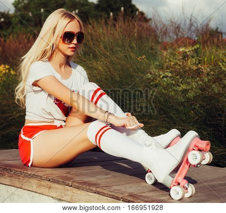Beautiful young blonde sexy girl tighten the laces sitting on a bench in a vintage roller skates, wearing shorts, golfs, sunglasses and a T-shirt. Hot summer day. Outdoor.