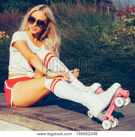Portrait of a beautiful tanned young blonde girl tighten the laces sitting on a bench in a vintage roller skates, sunglasses wearing shorts, golfs and a T-shirt. Looking at camera. Hot summer day. Outdoor.