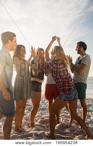 Happy friends dancing together on the beach