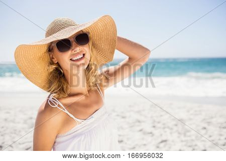 Portrait of blonde woman with straw hat on the beach