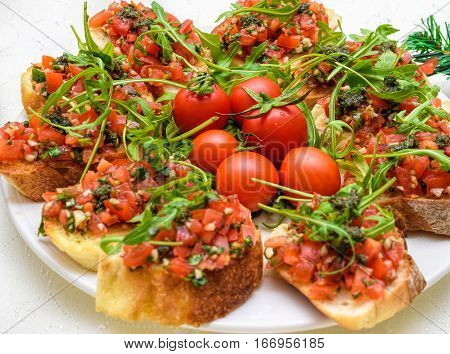 Tasty savory tomato Italian appetizers, or bruschetta, on slices of toasted baguette garnished with pesto and ruccola salad