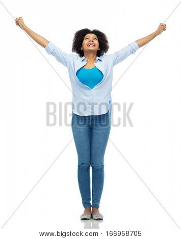 people, success and portrait concept - happy african american young woman with raised fists looking up over white