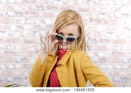 beautiful young blonde woman with a yellow jacket and sun glasses