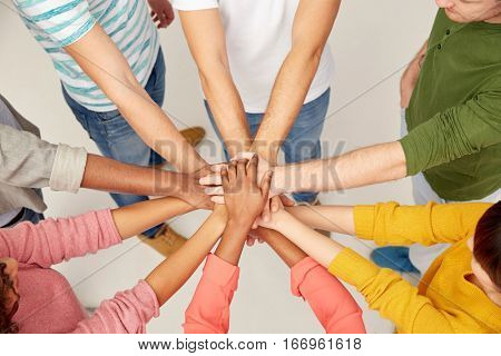 friendship, teamwork and people concept - group of international men and women with hands on top of each other