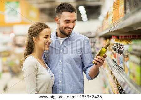 shopping, food, sale, consumerism and people concept - happy couple buying olive oil at grocery store or supermarket