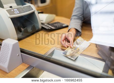 people, withdrawal, money, saving and finance concept - clerk with swiss francs cash at bank office or currency exchanger
