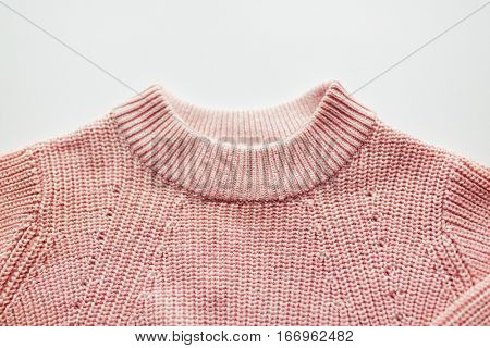 clothes, fashion and objects concept - close up of sweater or pullover on white background