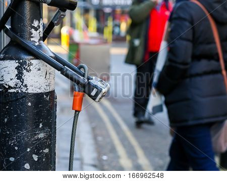 Broad Street Oxford United Kingdom January 22 2017: U-lock secure bicycle locks on light post on Broad street Oxford city centre England
