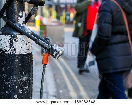 Broad Street Oxford United Kingdom January 22 2017: U-lock secure bicycle locks on light post on Broad street Oxford city centre England
