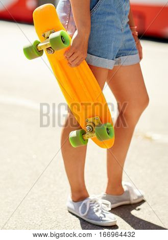 summer, extreme sport and people concept - teenage girl with short modern cruiser skateboard on city street