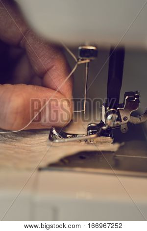 closeup of a young man threading the needle of a sewing machine
