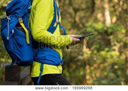 young woman hiker reading ebook on forest trail while have rest