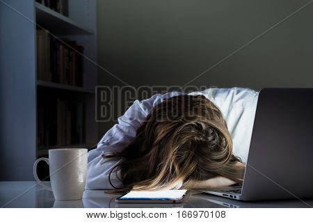 Tired person sleeping at desk in home office with turned on computer and tablet PC. Exhausted female person taking nap in dark room of home office overworking with laptop