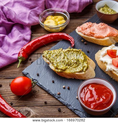 Sandwiches with various fillings for breakfast on wooden table with sauces, chili